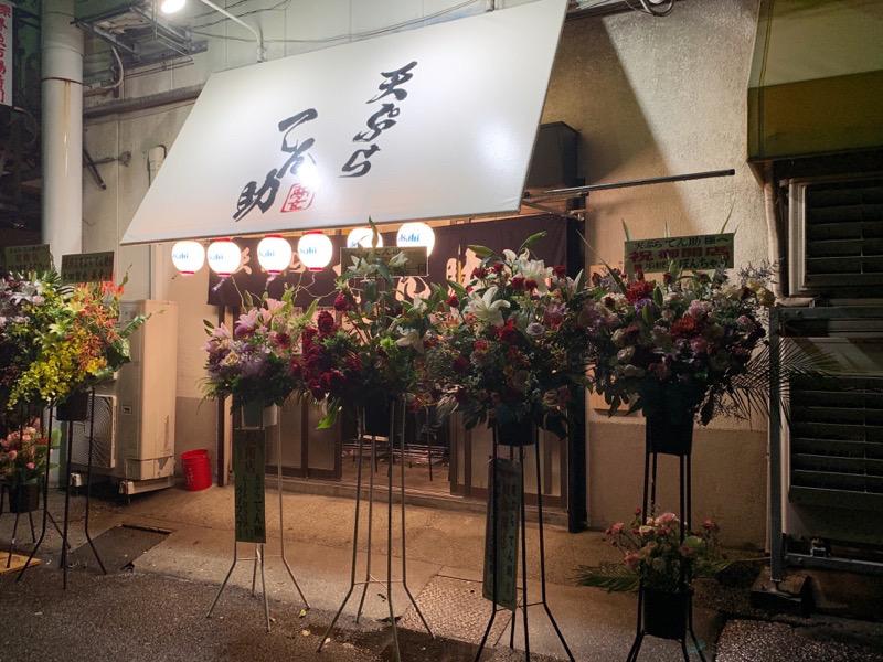 堺魚市場の『天ぷらてん助』の外観の写真 開店祝いの花が飾られている様子